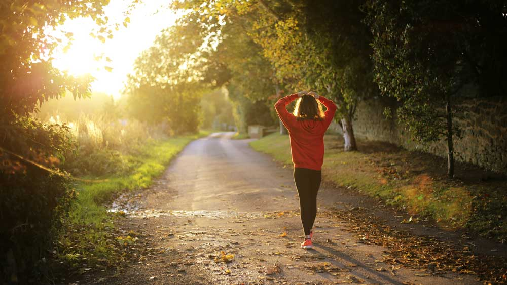 The backside of a healthy woman walking down a peaceful dirt road surrounded by trees during the sunrise