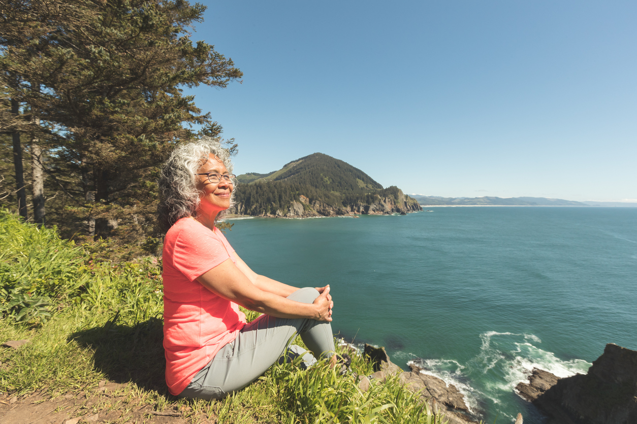 A happy smiling senior woman relaxes on the rocks by a cliff overlooking the ocean. A forested mountain range is behind her.